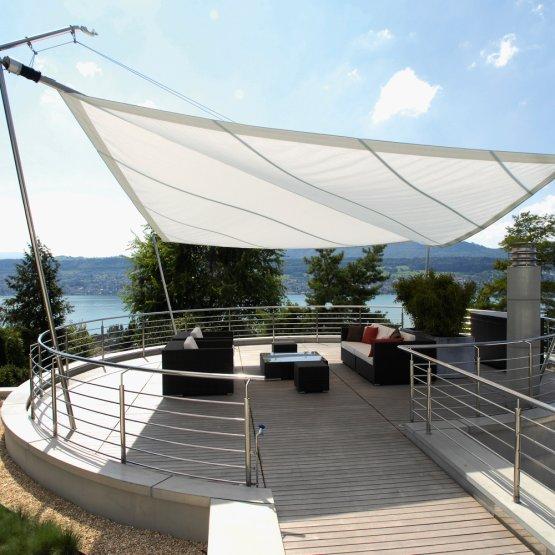 SunSquare Dreiecksegel über einer runden Terrasse.
